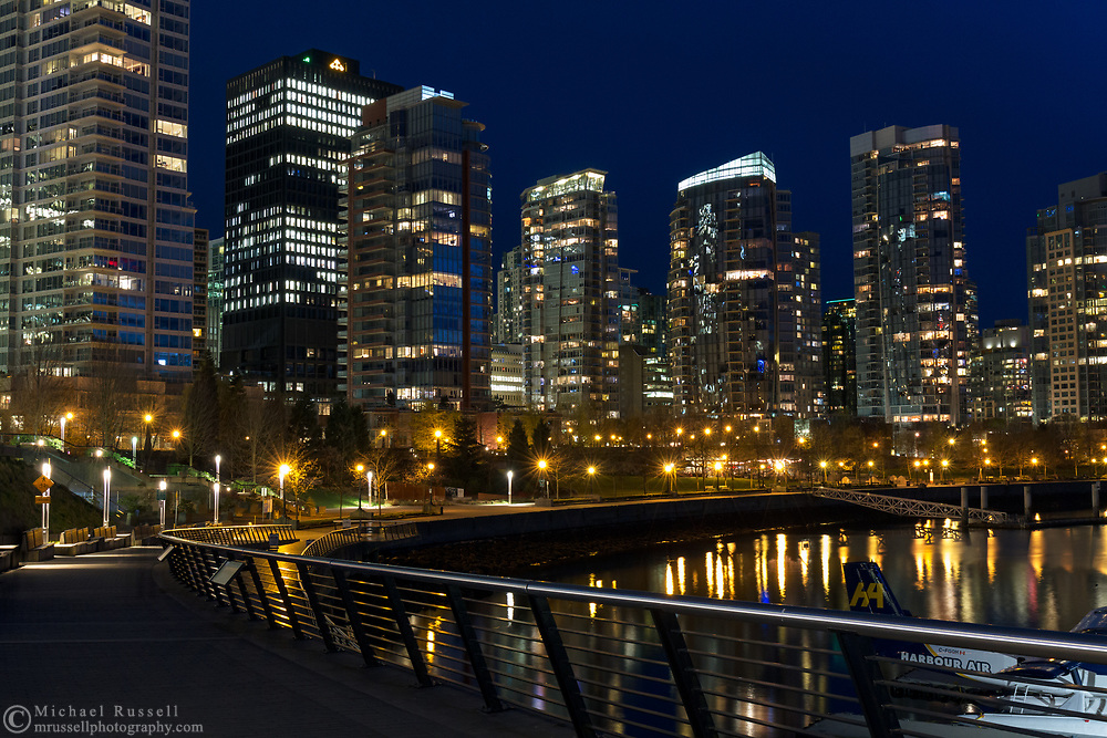 The Seawall of Vancouver and west end apartment and condo towers at Coal Harbour.  Photographed from the Seawall next to Vancouver Harbour Flight Centre in Vancouver, British Columbia, Canada.