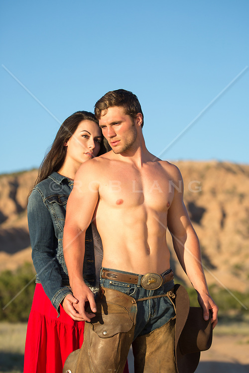 shirtless muscular cowboy with a girl outdoors