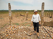 02 APRIL 2016 - NA SAK, LAMPANG, THAILAND:  A Thai woman walks through the ruins of the old public health clinic in Sobjant village. The village of Sobjant in Na Sak district in Lampang province was submerged when the Mae Chang Reservoir was created in the 1980s. The village was relocated to higher ground a few kilometers from its original site. The drought gripping Thailand drained the reservoir and the foundations of the Buddhist temple in the original village became visible early in 2016. Thai families come down to the original village to pray in the ruins of the temple and look at what's left of the village. This is the first time in more than 30 years that this area has not been under two meters of water.     PHOTO BY JACK KURTZ