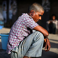 A rickshaw driver in Delhi, India waits for medical attention after having his ear cut off.