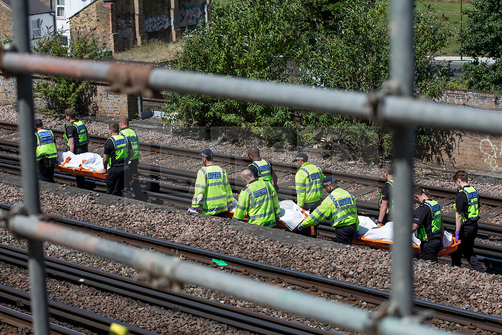 © Licensed to London News Pictures. 18/06/2018. London, UK. Police carry three bodies away from the train tracks near Loughborough Junction station after three bodies were discovered after they were reportedly hit by a train. Photo credit: Rob Pinney/LNP