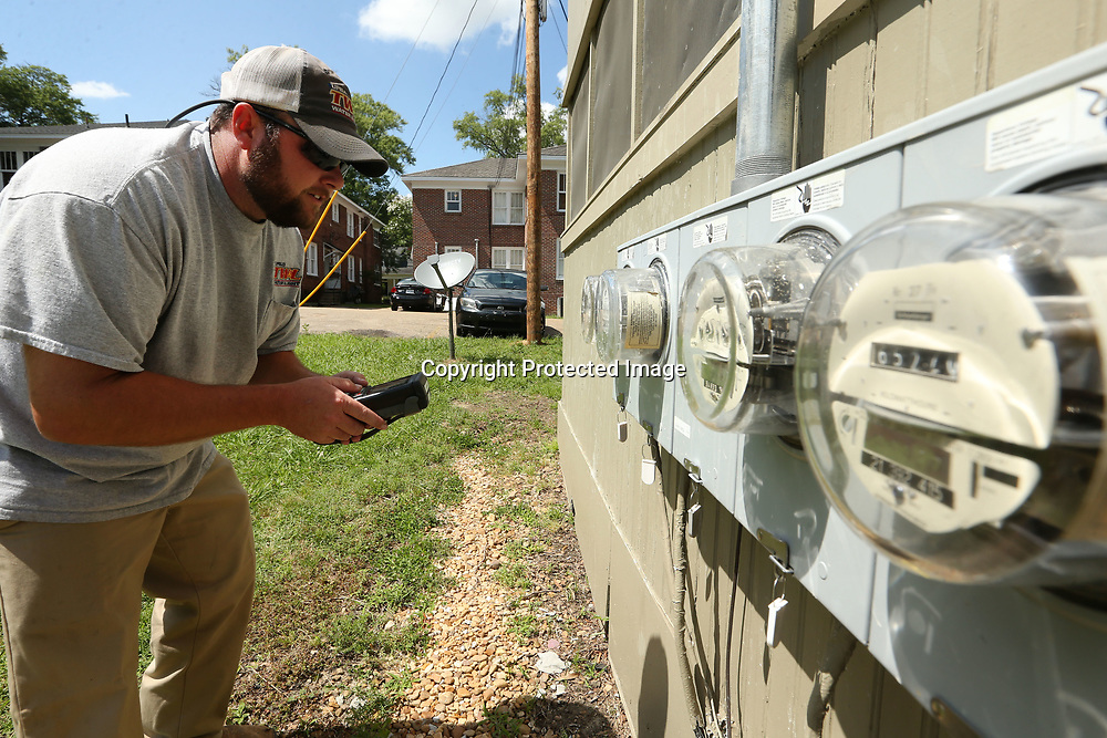 Matthew Holt, Meter Reading Supervisor at Tupelo Water and Light, checks the meters at an apartment complex on Green Street Wednesday afternoon.