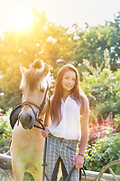 Portrait of young beautiful woman standing with horse in ranch