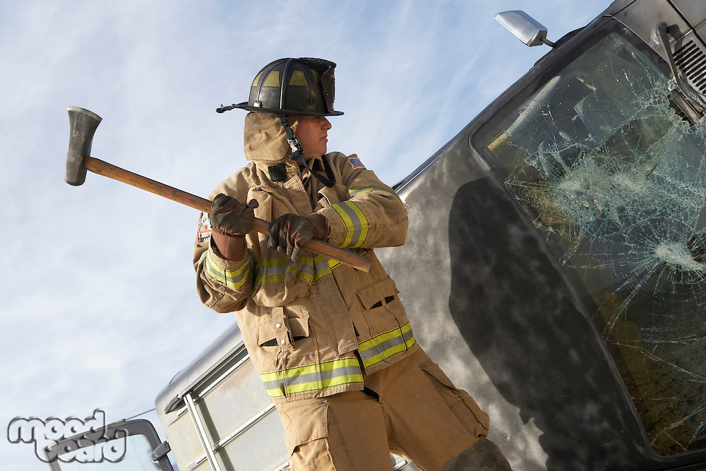 Firefighter hitting crashed car with axe