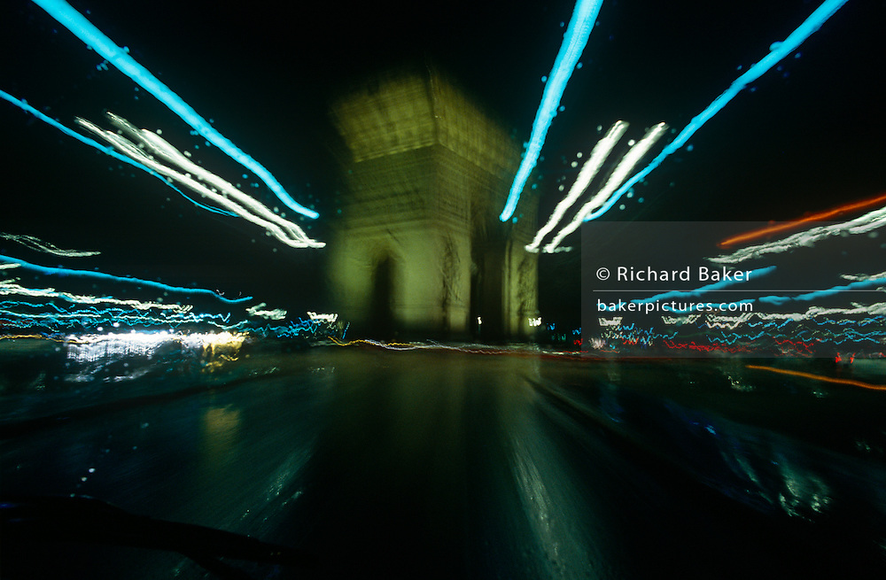 A zoomed and blurred landscape at night of Paris' l'Arc de Triomphe