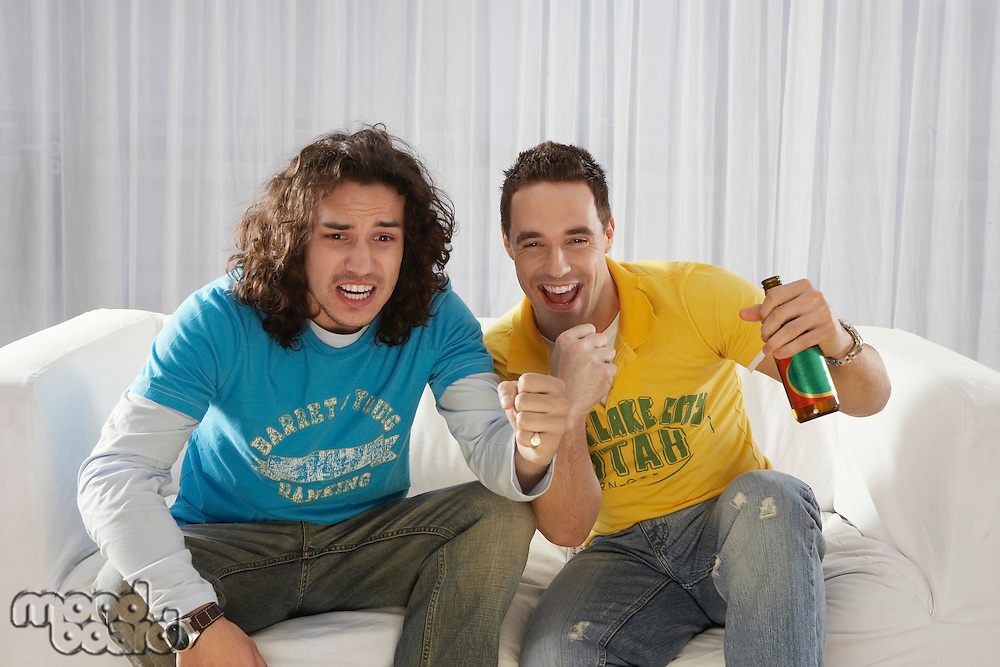 Two men sitting on sofa watching television and cheering with beer bottle