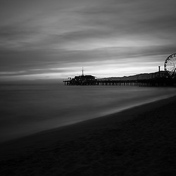 Santa Monica Pier sunset black and white photo along the Pacific Ocean in Southern California. Copyright ⓒ 2017 Paul Velgos with All Rights Reserved.