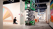 Behind the scenes, gallery workers prepare booths at Art Basel Miami Beach 2011
