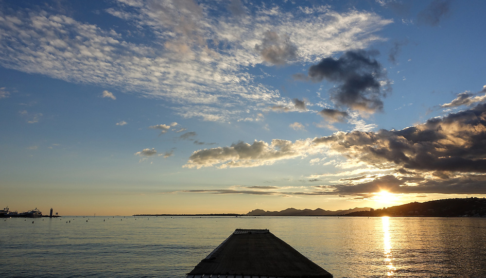 A yellow settting sun hovers above a pier in the Mediterranean Sea on the French Riviera at Juan-les-Pins. White scattered clouds float above in a blue sky.