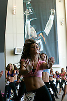 Prospective Denver Broncos cheerleaders practice under a giant photo of John Elway holding up the Super Bowl trophy on the first day of auditions in Denver, Colorado March 25, 2007.  Over 250 women applied for the 34 slots. REUTERS/Rick Wilking (UNITED STATES)