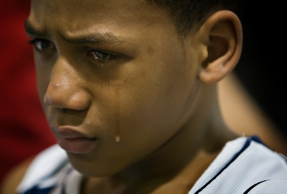 Troy Simon, one of Amir Clemons' basketball teammates, wept during a brief ceremony after the first points of a basketball game at the Girls & Boys Club at 43rd and Cleveland on Friday night. The Blazers basketball team that Amir Clemons played for retired his jersey number, #15, along with his younger brother's, Gerard, #00, after both were part of the quadruple homicide last week in Raytown.