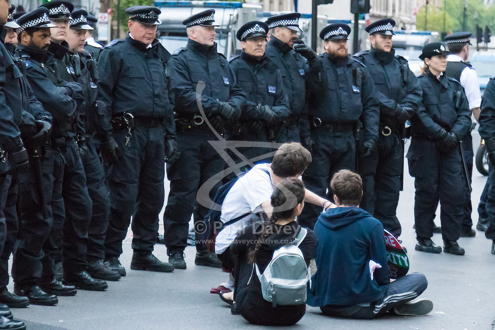 London, May 27th 2015. Protesters sit in the middle of Whitehall surrounded by riot police as they demonstrate outside Downing Street following a march through the capital's streets, against the Tories' ongoing campaign of austerity on the day the Queen delivered her speech to Parliament