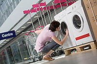Young woman looks inside tub of washing machine in shopping mall Voronezh