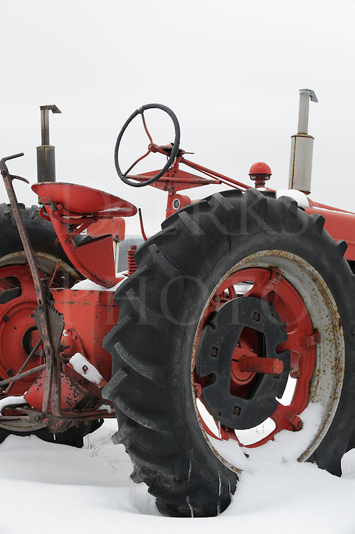 Old farm tractor sitting outside in the snow, used agricultural equipment on outside display in Pennsylvania, PA, USA.