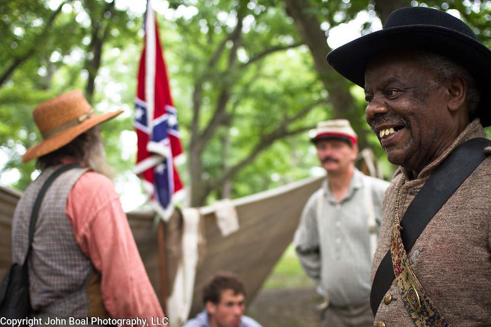 "Tom Spruill, who grew up in New York City, but now lives in Waynesboro, PA, chats with fellow reenactors and living historians, at a Confederate encampment, during the Sesquicentennial Anniversary of the Battle of Gettysburg, Pennsylvania on Wednesday, July 3, 2013.  Spruill started participating in these events 2 years ago in order to spread the story of free men of color serving in the Confederate Army.  ""They didn't fight for the South, they fought because they lived in the south..."", arguing that most of the black Confederate soldiers weren't slaves, but owned property and fought to protect their land.  Evidence for the black Confederate soldier is controversial.  Some claim the evidence is negligible, while others maintain the denial of black participation in the Confederate cause is another example of Northern prejudice toward the South.   John Boal Photography"