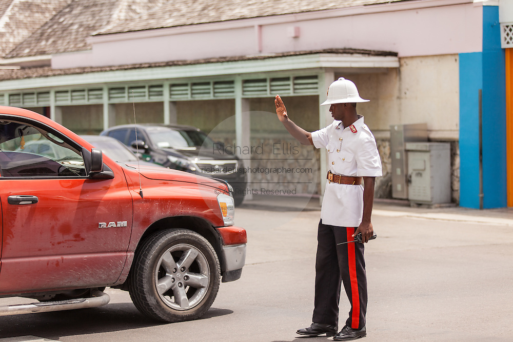 A member of the Royal Bahamas Police wearing a Wolseley pith helmet directs traffic in Nassau, Bahamas.