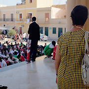 Eritrean refugees praying outside the main church during a demonstration against their fingerprints being taken in Lampedusa