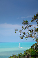 A lone boat sits just offshore from Airlie Beach as an approaching storm turns the seas a luminous turquiose.