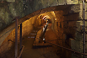 Underground tunnels, 13th century, linking 2 wells, 1 of which has a 19th century hydraulic pump which is still in working order, which pumped the saline water up from the layer of rock salt 250m below ground, in the Museum of Salt or Musee du Sel, designed by architects Malcotti-Roussey and opened May 2009, in the Great Saltworks at Salins-les-Bains, Jura, Bourgogne-Franche-Comte, France. 15th century saltworks were replaced by industrial buildings in the 18th century, where saline water was pumped from underground wells and evaporated to form salt. Saline water was also piped from here from 1780 until 1895 through 21km of wood then cast iron pipes to the Royal Saltworks or Saline Royale at Arc-et-Senans to be processed. The saltworks at Salins-les-Bains ceased production in 1962 and are now listed as a UNESCO World Heritage Site. Picture by Manuel Cohen