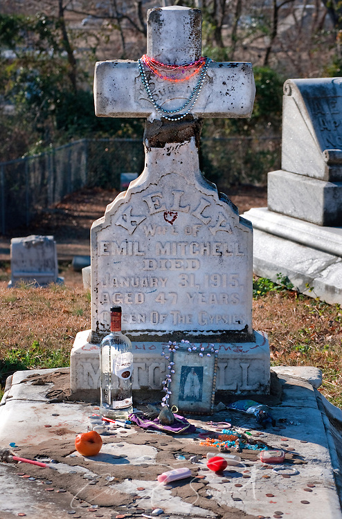 Mardi Gras beads decorate the headstone of gypsy queen Kelly Mitchell at Rose Hill Cemetery in Meridian, Mississippi. Mitchell was a member of the Gypsy Royal Family, many of whom are buried nearby. Tourists and visitors often leave gifts of fruit, trinkets, and liquor on the family's graves. (Photo by Carmen K. Sisson/Cloudybright)