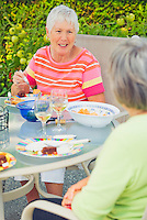 Two mature women sitting at outdoor patio table eating a meal