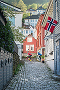 Two bicylists peddle down a street in Bergen during the celebration of Syttende Mai, Norway's Constitution Day, celebrated on May 17th.