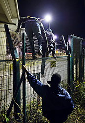 © Licensed to London News Pictures. 09/08/2015. Calais, France. Migrants attempt to access the train tracks to the Eurotunnel terminal at Frethun near Calais, northern France through a hole in a fence. Hundreds of migrants attempt to illegally access the Eurotunnel complex each night in order to board a train and reach the UK. Photo credit: Ben Cawthra/LNP