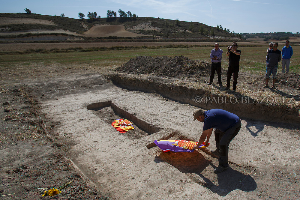 24/09/2017. A member of The Soria Association for Memory and Dignity places a Republican flag on a empty mass grave after archeologists recovered the bodies of 7 people from the mass grave known as 'La Fosa de los Maestros' (The teachers' mass grave) in a field in Cobertelada on September 24, 2017 near Almazan, in Soria province, Spain. The seven people where allegedly assassinated on August 25, 1936 after being take from prison of Almazan during the Spanish Civil War by Falangists, as part of General Francisco Franco armed forces. The remains are supposed to belong to teachers in the region, who were also friends of Spanish writer Antonio Machado. The exhumation was done by members of ARANZADI and La asociacion Soriana Recuerdo y Dignidad (ASRD) 'The Soria Association for Memory and Dignity'. Spain's Civil War took the lives of thousands of people on both sides and civilians, but Franco continued his executions after the war has finished. Teachers, as part of the education sector, were often a target of Franco's forces. Spanish governments has never done anything to help the victims of the Civil War and Franco's dictatorship while there are still thousands of people missing in mass graves around the country. (© Pablo Blazquez)