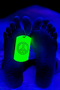 Peace symbol toe tag on a body in a morgue.Black light
