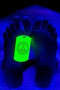 Peace symbol toe tag on a body in a morgue.Black light