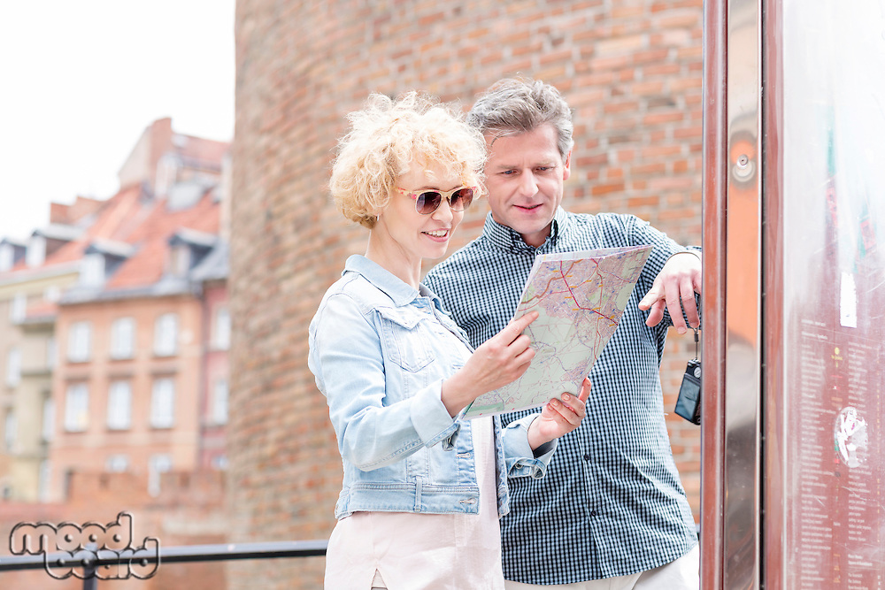 Smiling middle-aged couple reading map in city