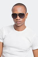 Portrait of confident young man wearing sunglasses against white background