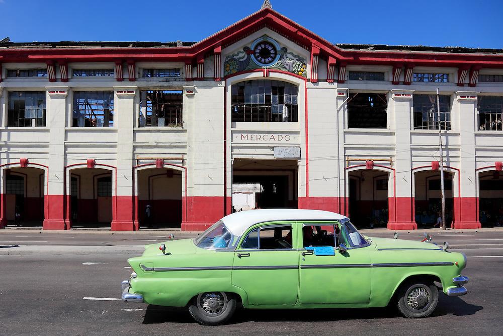 Car passing an old market in Havana Vieja, Cuba.