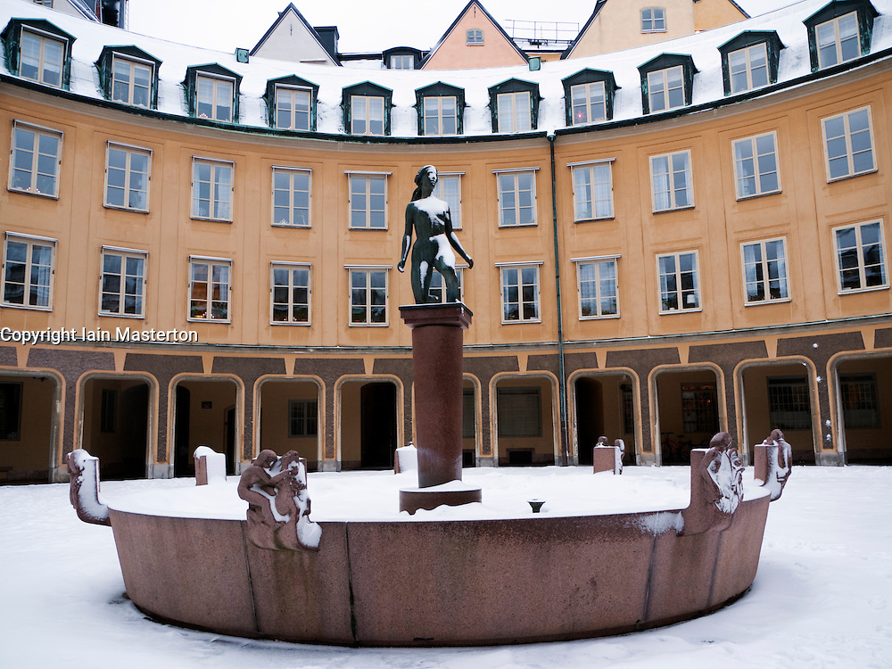 Ornate staute and residential courtyard in Gamla Stan old town district in winter in Stockholm Sweden