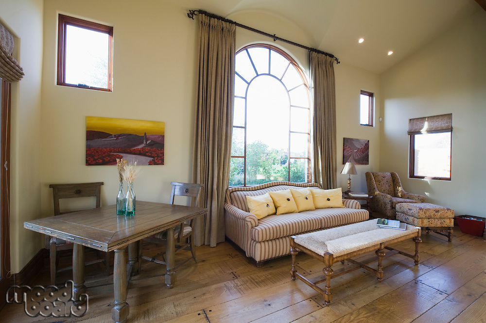Arched window and sofa in living room with high ceiling