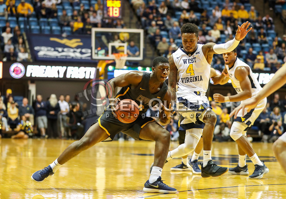 Dec 20, 2017; Morgantown, WV, USA; Coppin State Eagles forward Adam Traore (0) drives towards the basket while guarded by West Virginia Mountaineers guard Daxter Miles Jr. (4) during the first quarter at WVU Coliseum. Mandatory Credit: Ben Queen-USA TODAY Sports
