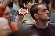 """A member of the audience holds up her phone with the word """"Disagree"""" during a heated discussion with U.S. Sen. Tim Scott and U.S. Rep. Mark Sanford at a town hall meeting February 18, 2017 in Mount Pleasant, South Carolina. Hundreds of concerned residents turned up for the meeting to address their opposition to President Donald Trump during a vocal meeting held by U.S. Rep. Mark Sanford and Senator Tim Scott."""