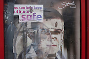 Detail of a defaced Southwark Council anti-crime poster on the window of an old phone kiosk, on 4th January, at Elephant & Castle, London, England.