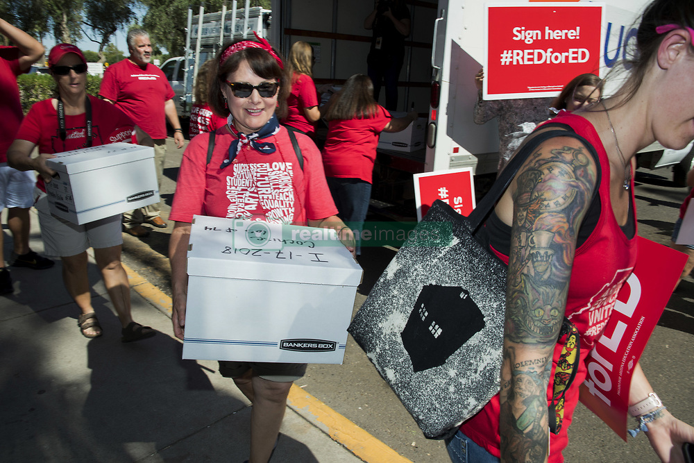July 5, 2018 - Phoenix, Arizona, U.S - Supporters of better funding for Arizona schools delivers petitions to the Arizona Secretary of state's office for a ballot measure asking for an income tax on higher wage earners to drastically improve funding to education in the state. Arizona has ranked 49th in the nation for its education system in recent years, as teachers continue to deal with declining facilities conditions, and have to work two jobs in order to survive. The Red for Ed movement collected more than 270,000 signatures. (Credit Image: ©  via ZUMA Wire)