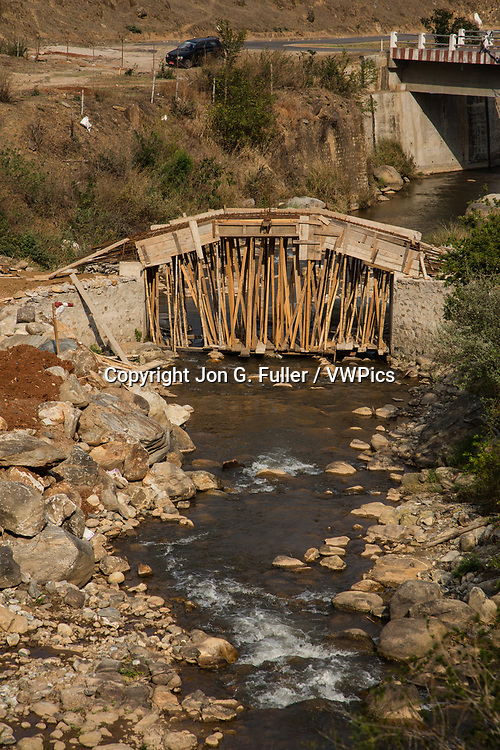 A new foot bridge across a creek is under construction near Sopsokha, Bhutan.  Wooden supports have been placed under the concrete forms.