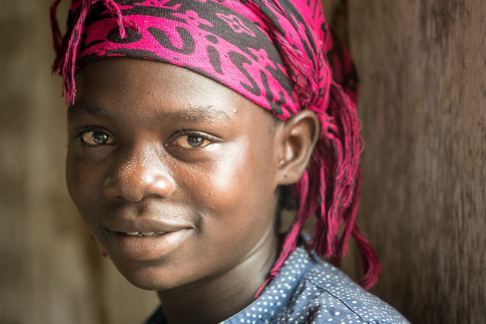 A close up image of a young girl with a wrap on her head in Ganta, Liberia