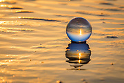 Crystal ball and it's reflection at sunrise on the beach at the Outer Banks , NC.