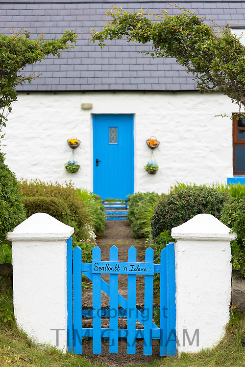 Traditional cottage with blue painted wooden front door and gate, slate tiles and front garden on Isle of Skye, the Western Isles of Scotland, UK
