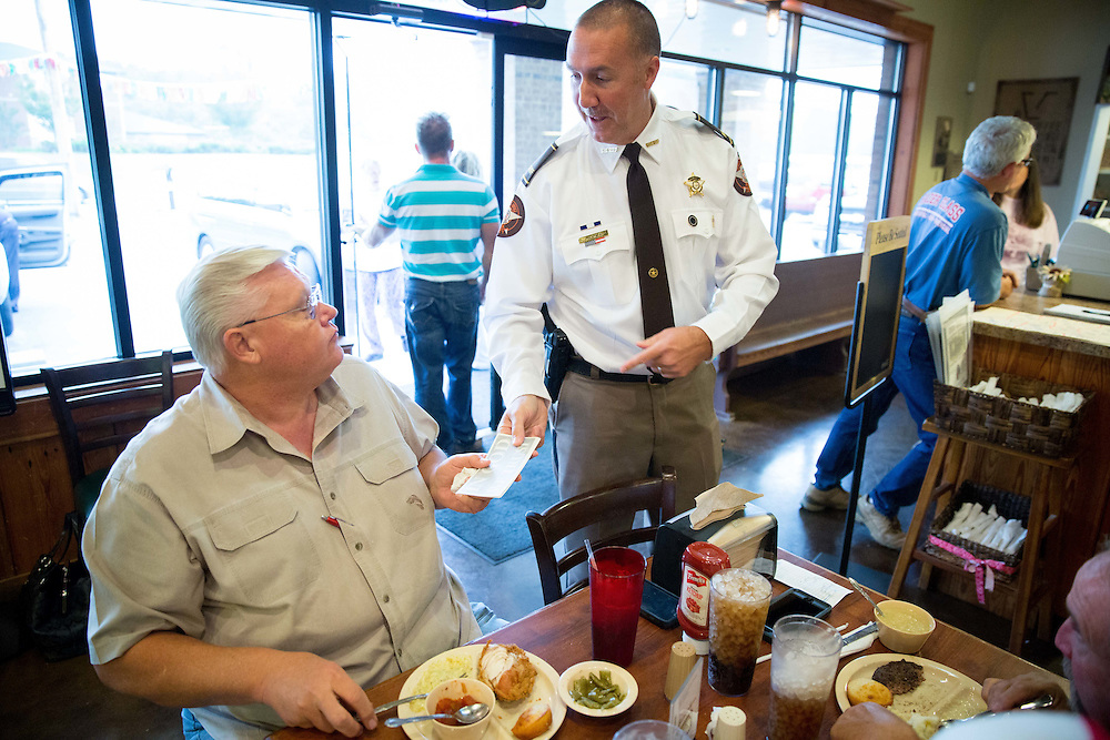 Polk County Sheriff Johnny Moats hands several bumper stickers that read &quot;In God We Trust&quot; to James Osborne at Gran-Gran's restaurant in Cedartown, Ga., on Thursday, Oct. 1, 2015. After affixing &quot;In God We Trust&quot; decals to his department's vehicles, Mr. Moats had stickers made that he sells to the public for $2, which sell out fast. More than 50 departments across the country have put the &quot;In God We Trust&quot;  decals on their cars in recent months. Photo by Kevin D. Liles for The New York Times<br /> <br /> <br />  talks with Mindy Cook, a server at Gran-Gran's restaurant in Cedartown, Ga., on Thursday, Oct. 1, 2015. Mr. Moats, who is very popular with county residents, is among law officers who have affixed &quot;In God We Trust&quot; decals to their cars. More than 50 departments across the country have done so in recent months. Photo by Kevin D. Liles for The New York Times