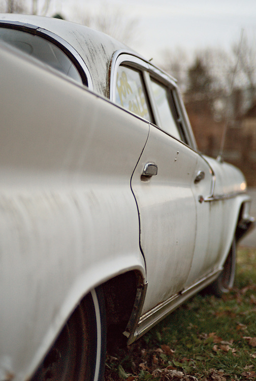 """Detail of white 1961 Chrysler four door sedan with """"for sale"""" written on window"""