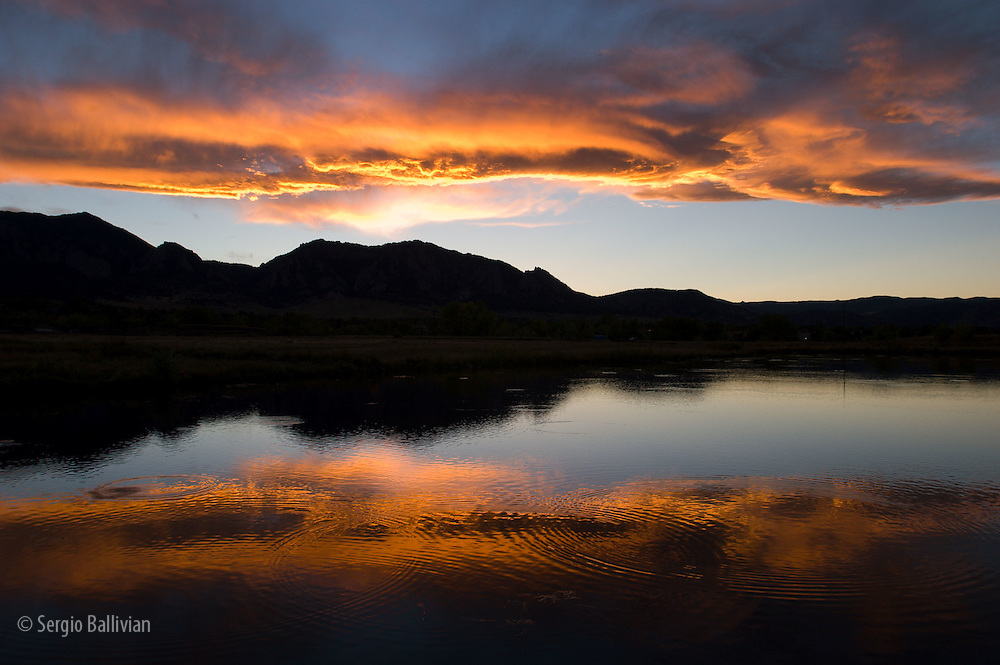 A sunset over the Rocky Mountains is reflected in a lake near Boulder, Colorado