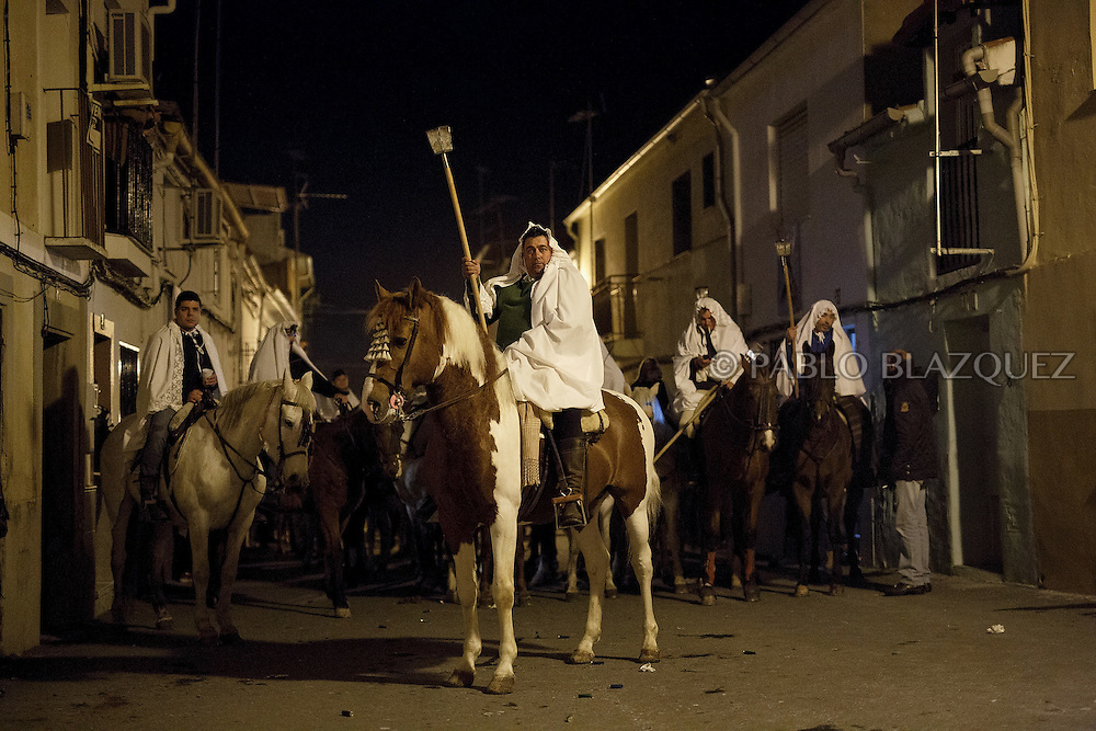 "Horsemen stop their march during the ""La Encamisa"" Festival on December 7,  2014 in Torrejoncillo, Extremadura region, Spain. ""La Encamisa"" is an ancient festival in honor of Immaculate Conception. Hundreds of horsemen wearing a white sheet gather outside the church in the main square. The procession starts when a banner with the image of Immaculate Conception is delivered to the horse rider steward and people cheer and shoot blanks. There are bonfires along the way where people gather to chat, eat traditional sweets and drink local wine. The origin of this tradition is unknown but it is believed the festival comes from a military event in which people from Torrejoncillo were involved. The war in Flanders in 1585, the Battle of Pavia or a legend of the siege suffered by city of Coria. (© Pablo Blazquez)"