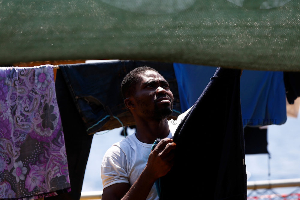A migrant hangs clothes to dry at the stern of the Medecins san Frontiere (MSF) rescue ship Bourbon Argos somewhere between Libya and Sicily August 8, 2015.  Some 241 mostly West African migrants on the ship are expected to arrive on the Italian island of Sicily on Sunday morning, according to MSF.<br /> REUTERS/Darrin Zammit Lupi <br /> MALTA OUT. NO COMMERCIAL OR EDITORIAL SALES IN MALTA