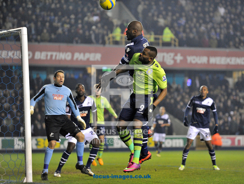Picture by Alan Stanford/Focus Images Ltd +44 7915 056117.25/01/2013.Danny Shittu of Millwall beats  Darren Bent of Aston Villa to the ball during the The FA Cup match at The Den, London.