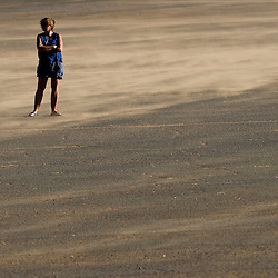 061611       Brian Leddy.A woman stands in the parking lot of Red Rock Park in a cloud of sand on Thursday night. Heavy winds area predicted through the weekend.